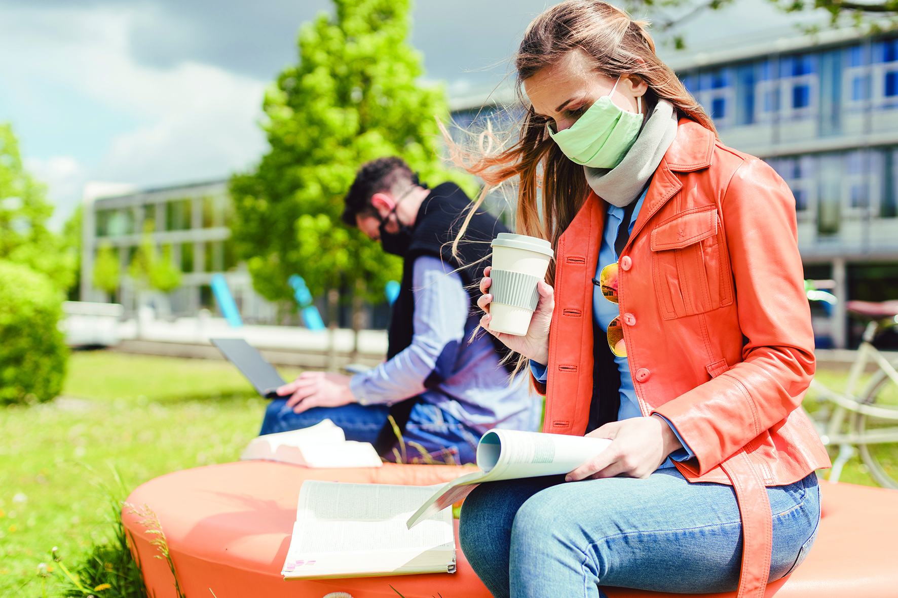 Woman sat with coffee cup on a bench with a mask on