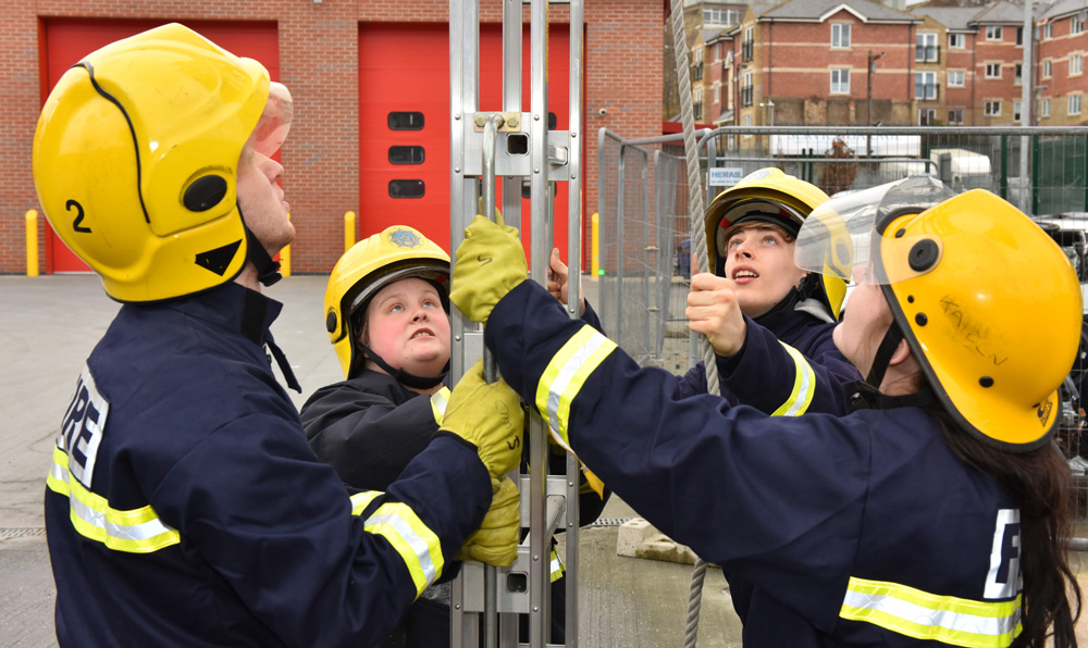 Students in uniform holding a ladder